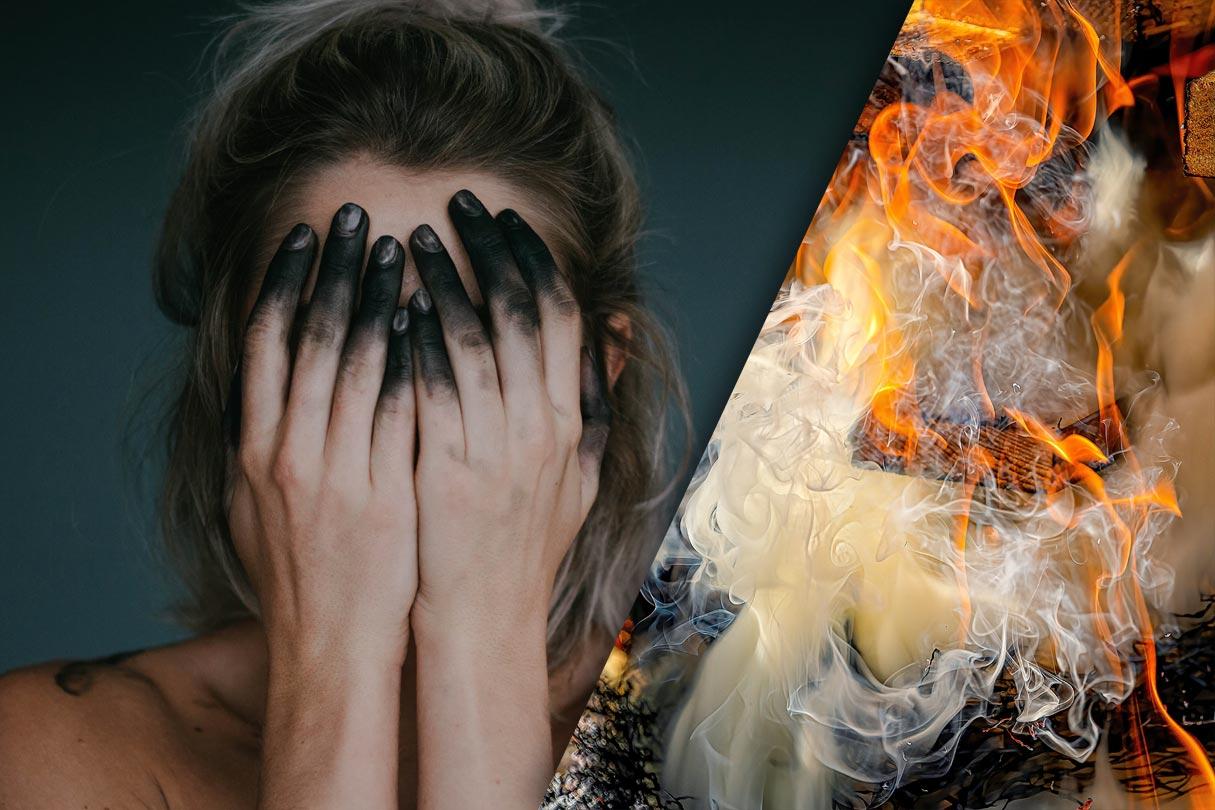 verzweifelte rußbefleckte Frau und qualmender Scheiterhaufen