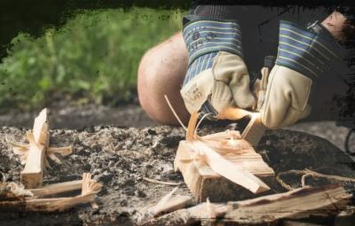 Bild zweier behandschuhter Hände, die ein Feuer entzünden