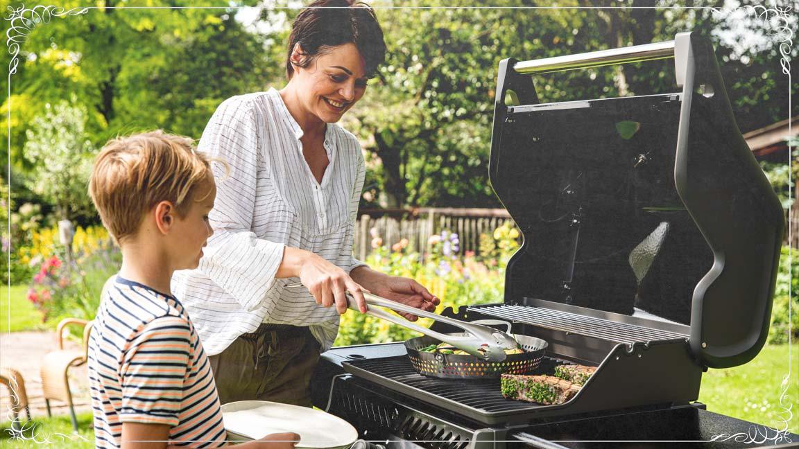 grillende Mutter gibt ihrem Sohn gegrilltes Gemüse