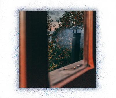 Blick durch Fenster auf rauchenden Schornstein