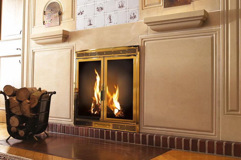 Ein Beispiel für eine eingebaute gold anmutende Kaminkassette mit einer mit Mamor getäfelten Wand.