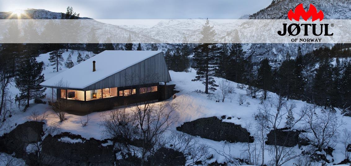 skandinavische Winterlandschaft mit einem Haus in dem ein Kaminofen von Jotul befeuert wird