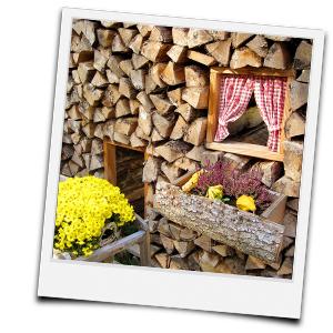 Brennholzmiete als Haus dekoriert