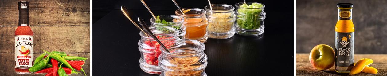 2 verschiedene BBQ Saucen mit unterschiedlichen Geschmacksrichtungen und ein paar Gläser mit erlesenen Zutaten
