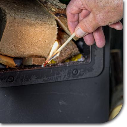 Ofen wird mit Streichholz angezündet