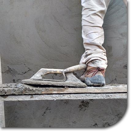 Mann auf Gerüst beim verputzen einer Wand
