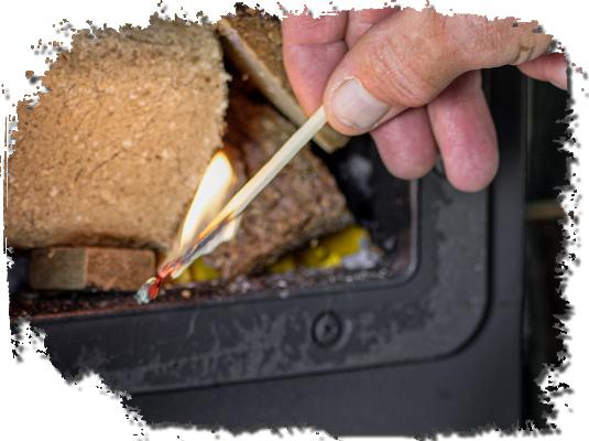 Foto eines offenen Ofens welcher mittels Streichholz angezündet wird